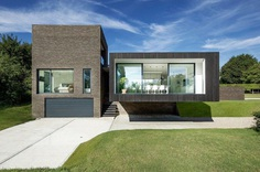Black Modern House Consisting of Five Modules Clustered Around a Central Courtyard 5