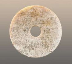 AN INTERESTING PARTLY CALCIFIED BI DISC WITH A GLASSY POLISH AND AN INCISED PATTERN OF LINKED SCROLLS