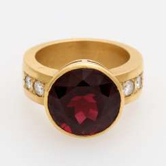 Ladies ring set with a round faceted garnet