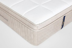 DreamCloud's white hybrid mattress with pillows