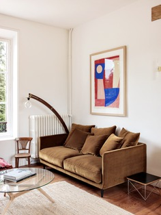 A painting by Caroline Denervaud hangs over another AM.PM sofa.