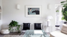 white living room with two leather chairs a glass coffee table and a few plants
