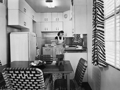 A woman cooks in a small 1940s-era kitchen. Bettmann/Getty Images