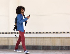 Smiling young black man walking with bag and mobile phone