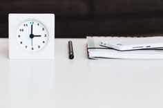 A clock, a notebook and a smartphone on a white desk