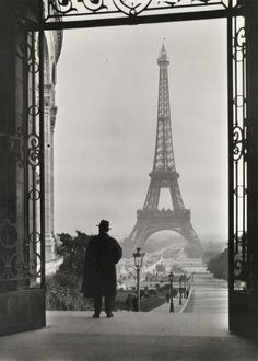 Man looks out on the Eiffel Tower.Photograph by Clifton R. Adams, National Geographic #eiffel #white #black #tower #photography #vintage #and #man #suit #50s