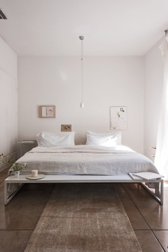 Designer Michaela Scherrer's bed feels spacious even though the bed takes up most of the room. That's because both her bed and the art on the walls are positioned toward the lower half of the room, leaving the upper half virtually empty. The single bulb hanging from the ceiling also serves to emphasize the height of the room. Photograph by Matthew Williams from Remodelista: A Manual for the Considered Home.