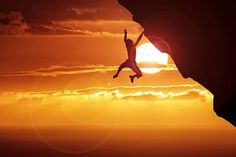 Silhouette Man Hanging On Cliff Against Sky During Sunset