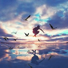 Boy jumping over sea with birds