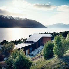 A remote house next to a lake and mountains | Murray Mitchell #roofs #butterfly #wood #architecture #landscapes #houses