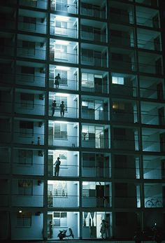People stand on their balconies in the night air, Singapore, 2001