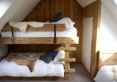 A bunk room with rustic wood and sumptuous linens.
