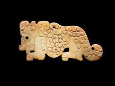 A SMALL, FLAT TIGER-SHAPED PENDANT IN WHITE JADE DECORATED WITH A JUANYUN PATTERN OF SCROLLS