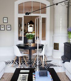 Matbordet är begagnat och målat svart. Stolar av Ray och Charles Eames. Vägglampa 265, Flos. Koskinnsmatta med zebratryck.