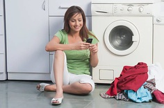 Woman text messaging near a washing machine