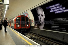 London, England, UK. St Paul's underground station. Cancer campaign poster featuring bald woman undergoing chemotherapy - Stock Image