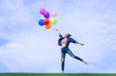 Young Woman Holding Colorful Balloons While Standing Against Sky