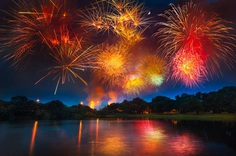 Colorful fireworks exploding above pond