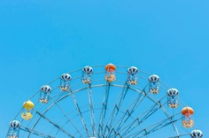 Close up of ferris wheel on blue sky. Travel, freedom, lifestyle concept. Vintage tone filtered.