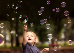 2 Year Old Fraternal Twin Boy Hold a Bubble Want and Plays with Floating Bubbles in a Park