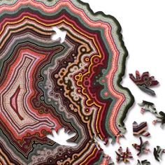 The intricate designs of these wooden jigsaw puzzles are generated by a computer algorithm and are modeled after the natural formations of agate stones. Each puzzle consists of approximately 180 irregular pieces with four crystal-themed pieces laser-cut from birch plywood. Once completed, it will come to about 8.5 inches. A stunning and one-of-a-kind challenge for the brain!