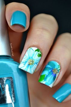 Blue floral nail art design. This pretty little nail art design sports a blue and white base colors with a lighter blue polish on top for th