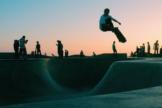 Skateboarder performing an aerial during sunset at Venice Skatepark in Los Angeles, California