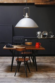Love the black cabinets and walls and how the appliances blend into it...especially against the wood table and awesome pendant light! #kitchen