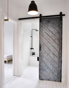 Black #reclaimedwood sliding #barndoor. #SwedishSummerHouse by #MrFrag. Photo by #TerenceChinPhotography. #slidingdoor