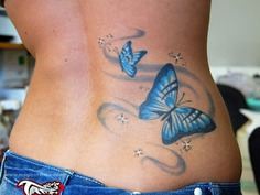 Butterfly tattoo with swirl on lower back for woman #tattoo