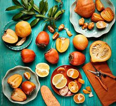 Still life of various orange colored fruits and vegetables on blue wood by trinettereed | Stocksy United