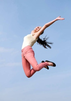 Low Angle View Of Young Woman Jumping Against Sky