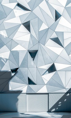 A pattern with gray and white triangles on a building facade in Madrid