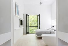 Master bedroom with whitewashed Douglas-fir floor and a balcony overlooking the tree canopy. Red Dirt Rd House by Amee Allsop. Photo by Glen