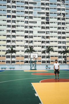 A man standing in a basket ball court with palm trees in front of a building