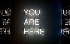 """A white neon reading """"you are here"""" on a wall"""