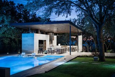 This modern steel, limestone, and wood outdoor pavilion has a living room, an outdoor kitchen with a bbq, and a dining area. #OutdoorLiving #OutdoorSpace