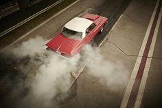 Classic car doing a burnout at a racetrack