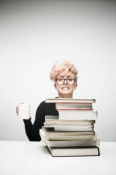 Young Woman Drinking Coffee Behind Pile of Textbooks