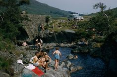 Bikes park near an arched stone bridge above bathers enjoying the water on Arran Island, Scotland, July 1965.Photograph by Robert Sisson, Na #bikes #americana #bathers #photograph #photography #vintage #film #scotland #1965