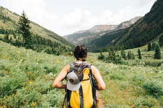 A woman with a large backpack on a trail in the mountains