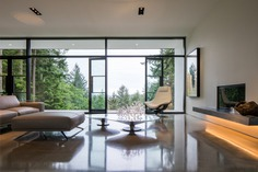 Collector's Retreat by Heliotrope Architects. Living Room, Concrete Floor, Coffee Tables, Chair, Sofa, Ceiling Lighting, Accent Lighting, Standard Layout Fireplace, Recessed Lighting, and Track Lighting Living Room
