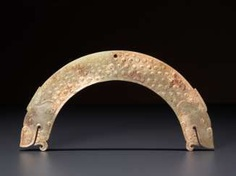 A FULLY DETAILED, RARE, SEMI-CIRCULAR , DRAGON-HEADED HUANG ARCHED PENDANT WITH A PATTERN OF RAISED SCROLLS