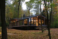 This rustic modern house in a forest has a modular design, with metal framing combined with barn board and glass to create a look that fits