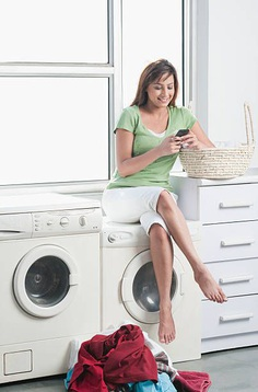 Woman sitting on a washing machine and text messaging on a mobile phone
