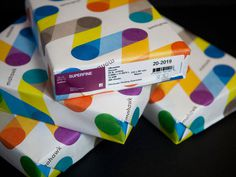Colorful patterns of the logo appear on ream wraps.