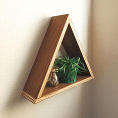 Wall hanging triangle shelf made from walnut plywood. By Corey Ward in collaboration with Love, Fannie Interiors.