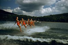 A womens water ski team lifts skis while being towed at 23 mph on Darts Lake in New York, 1956.Photograph by Robert Sisson, National Geogra