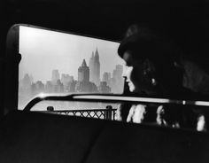 Departing from New York City as she crosses the 59th Street Bridge a shrouded woman gazes back at the iconic Midtown skyline in 1940..jpg (9 #vogue #white #woman #focus #dramatic #midtown #black #vintage #and #york #skyline #new
