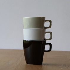 These stacking mugs boast a modern and sleek design. They are made of porcelain and feature a beautiful glaze handmade using a mix of natural tree ash and iron. Microwave and dishwasher-safe.